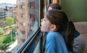 2 Kinder im Hochhaus am Fenster