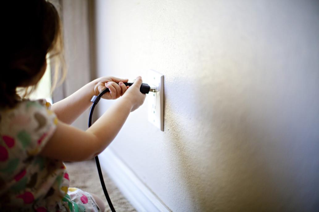 Kind spielt mit Steckdose